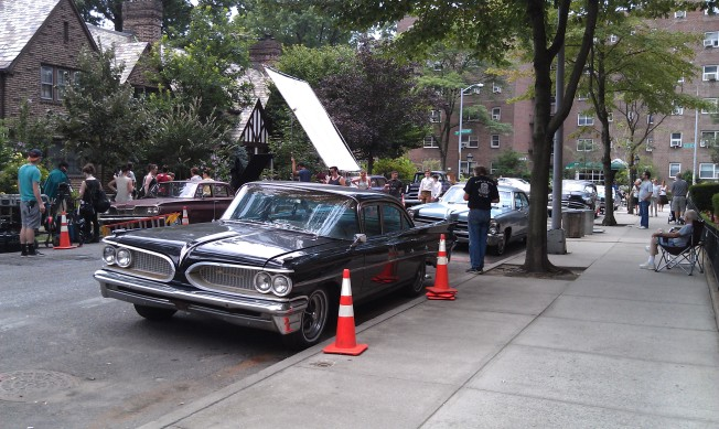 Moving further down the block, the filming is going on in front the large white screen in the background. Notice all of the cars are from the 50's and 60's.