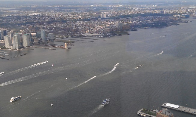Looking west, a series of boats sailing north on the Hudson River.